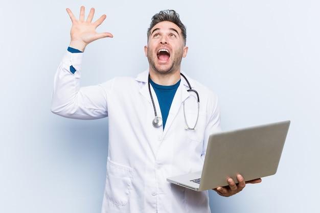 Hombre médico caucásico sosteniendo una computadora portátil celebrando una victoria o un éxito