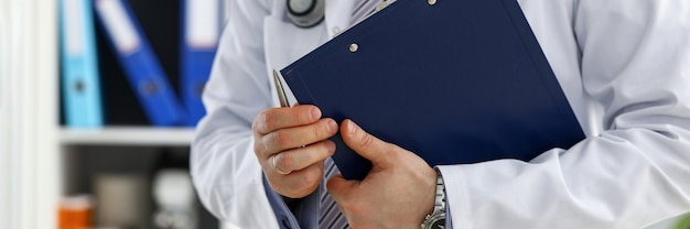 Hombre médico mano sostenga la almohadilla de documentos