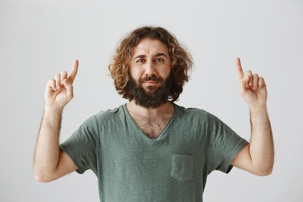 Hombre del medio oriente confundido y vacilante apuntando con el dedo hacia arriba y mirando preocupado