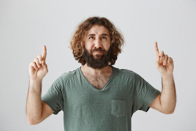 Hombre del medio oriente haciendo muecas decepcionado apuntando con el dedo hacia arriba y mirando con aversión