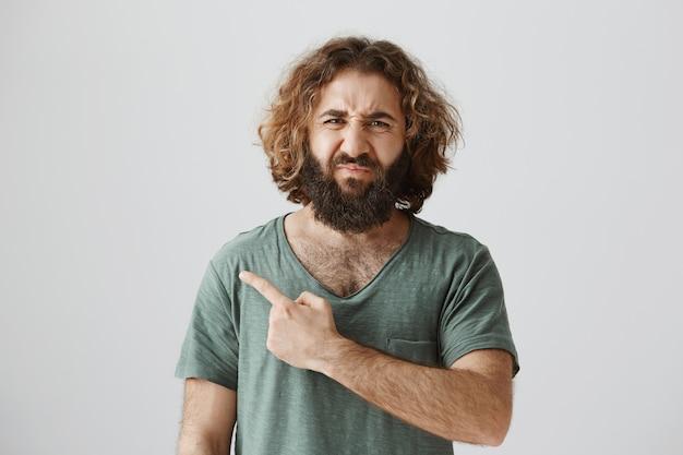 Hombre del medio oriente haciendo muecas disgustado y molesto que señala el dedo a la izquierda en algo malo