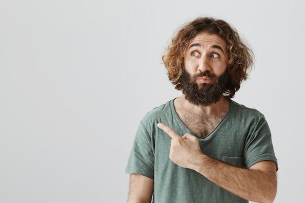 Hombre del medio oriente intrigado mirando y apuntando a la izquierda con entusiasmo