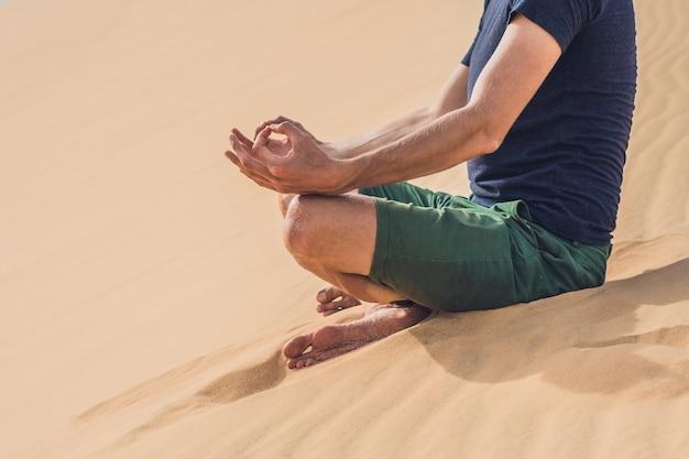 Un hombre está meditando sobre la arena en el desierto.