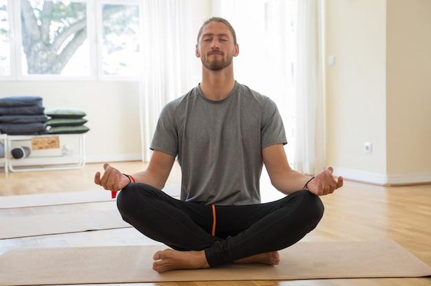 Hombre meditando y tomados de la mano en gesto mudra en clase