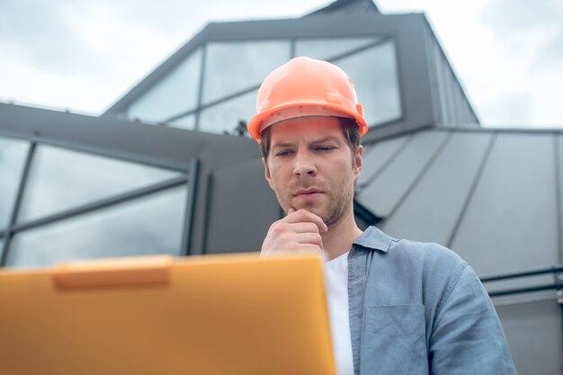 Hombre meditativo en casco de seguridad mirando boceto