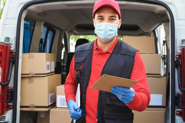 Hombre de mensajería delante de la furgoneta de carga que entrega el paquete al cliente