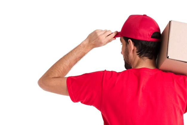 Hombre de mensajería de pie con caja y gorra desde el primer plano de disparo
