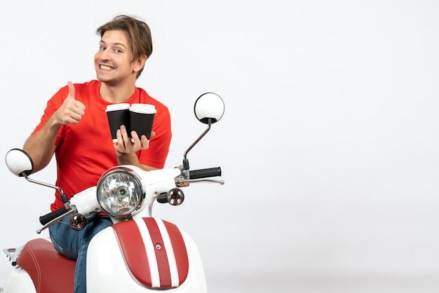 Hombre de mensajería sonriente joven en uniforme rojo sentado en scooter sosteniendo vasos de papel haciendo gesto ok en la pared amarilla
