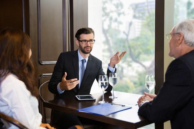 Hombre en una mesa de cristal exponiendo a un señor y una mujer