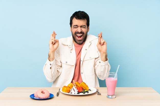 Hombre en una mesa desayunando gofres y un batido con los dedos cruzados