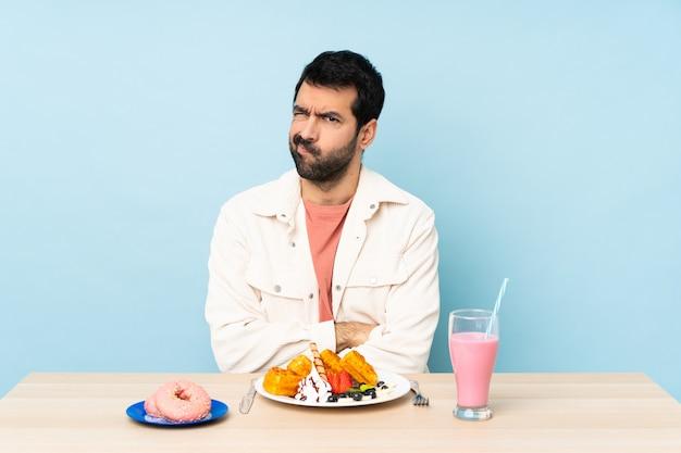 Hombre en una mesa desayunando gofres y un batido sintiéndose molesto