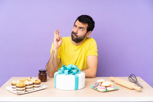 Hombre en una mesa con un gran pastel con los dedos cruzados y deseando lo mejor