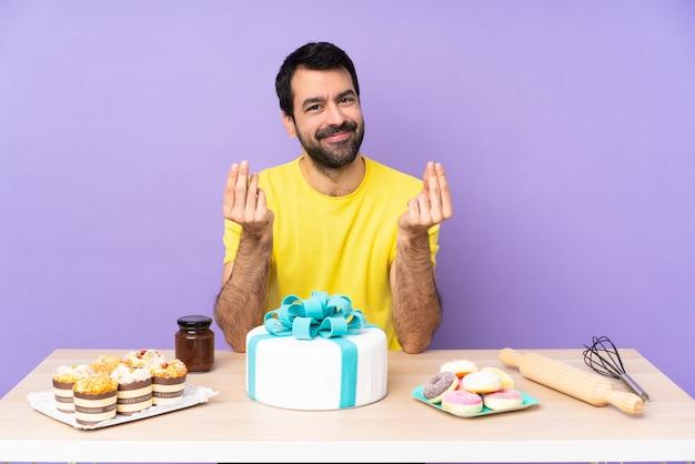 Hombre en una mesa con un gran pastel haciendo dinero gesto