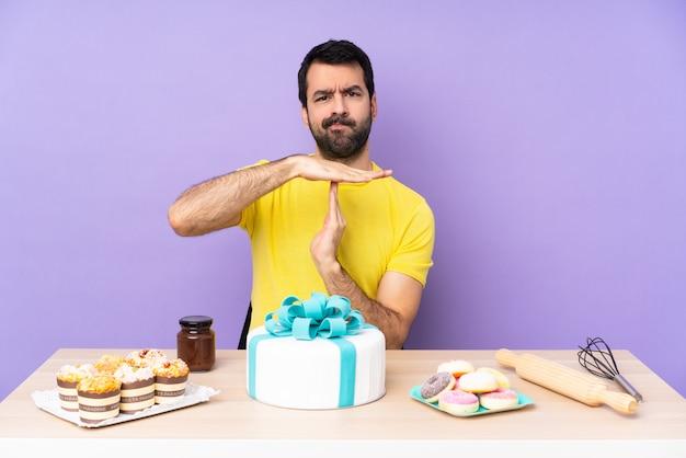 Hombre en una mesa con un gran pastel haciendo gesto de tiempo