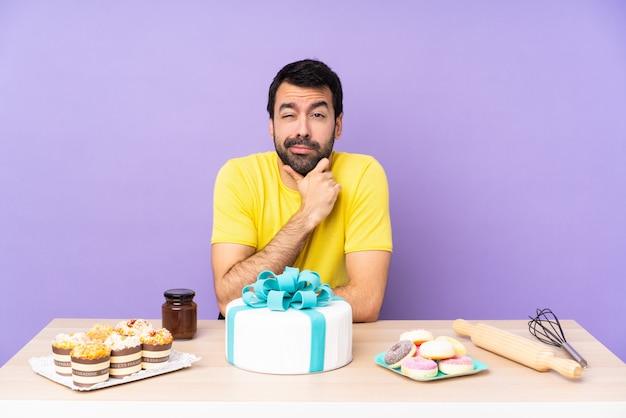 Hombre en una mesa con un gran pastel pensando