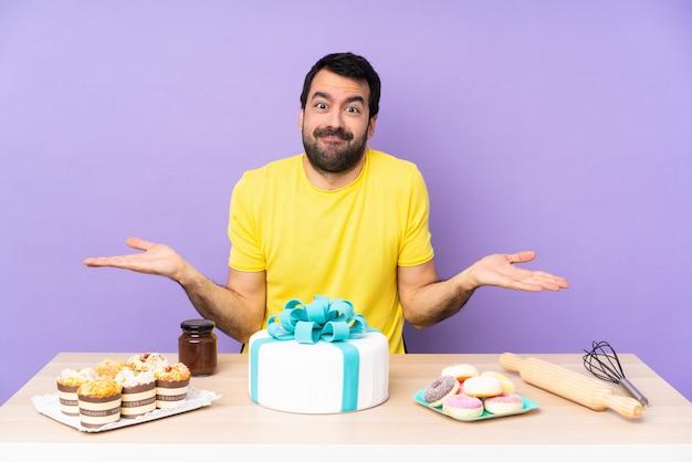 Hombre en una mesa con un gran pastel que tiene dudas mientras levanta las manos