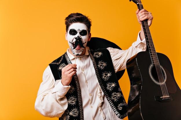 Hombre mexicano de ojos marrones con arte facial en forma de calavera grita emocionalmente, posando con falso bigote y guitarra en sus manos en la pared naranja.