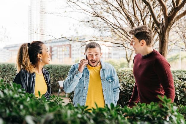 Hombre en mezclilla hablando por teléfono parado con amigos riendo