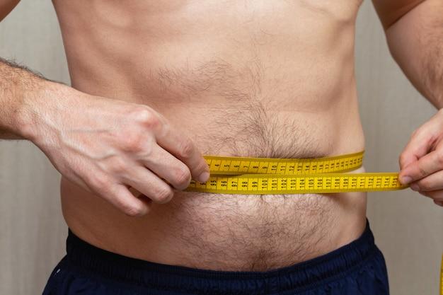 El hombre mide la cintura con una cinta amarilla. dieta fitness.