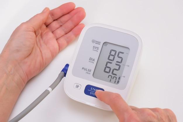 El hombre mide la presión arterial, fondo blanco. hipotensión arterial mano y tonómetro de cerca.