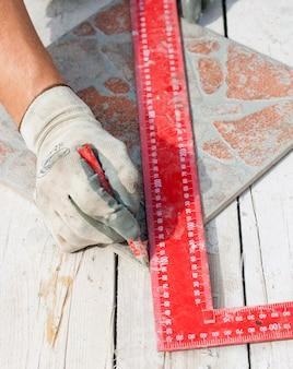 Hombre midiendo una pieza de azulejo con un lápiz