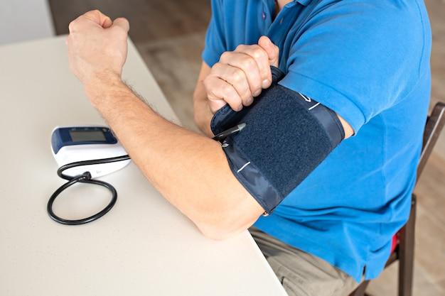 El hombre está midiendo la presión arterial.