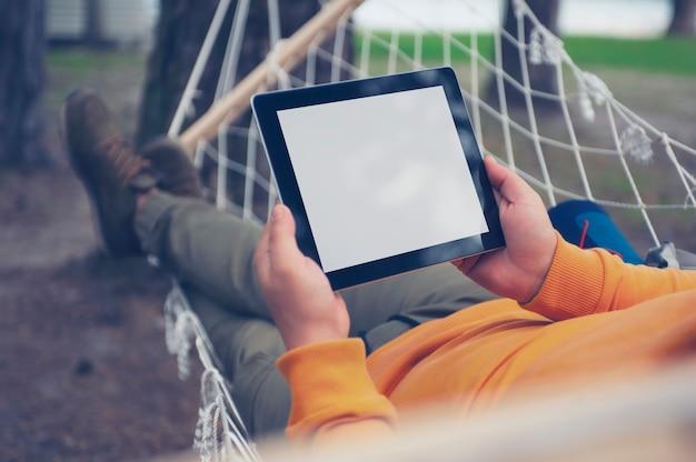 El hombre miente y descansa en una hamaca con una maqueta de una tableta con una pantalla blanca en sus manos.