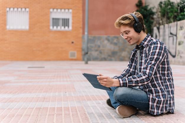 Hombre milenario haciendo conversación de video en pantalla táctil electrónica.
