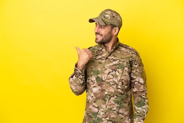 Hombre militar aislado sobre fondo amarillo apuntando hacia el lado para presentar un producto