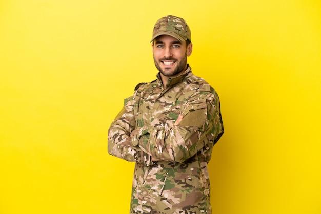 Hombre militar aislado sobre fondo amarillo con los brazos cruzados y mirando hacia adelante