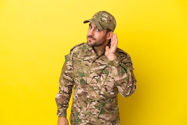 Hombre militar aislado sobre fondo amarillo escuchando algo poniendo la mano en la oreja
