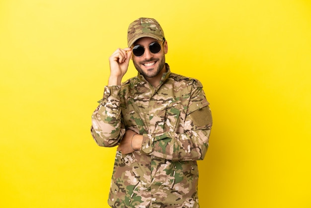 Hombre militar aislado sobre fondo amarillo con gafas y feliz