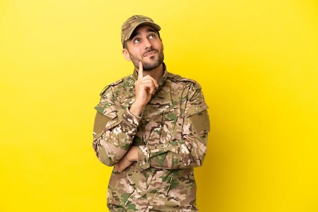 Hombre militar aislado sobre fondo amarillo pensando en una idea mientras mira hacia arriba