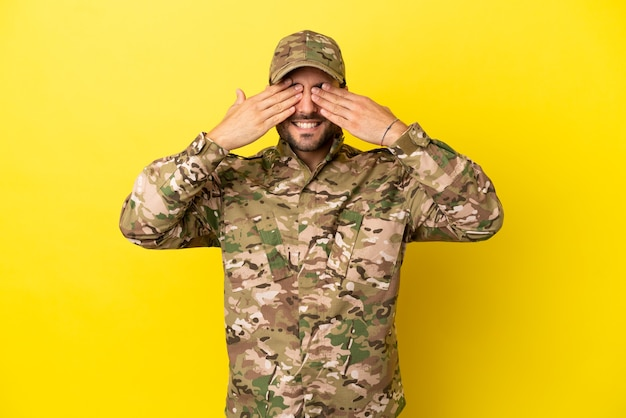 Hombre militar aislado sobre fondo amarillo que cubre los ojos con las manos