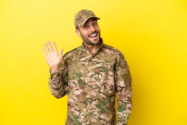 Hombre militar aislado sobre fondo amarillo saludando con la mano con expresión feliz