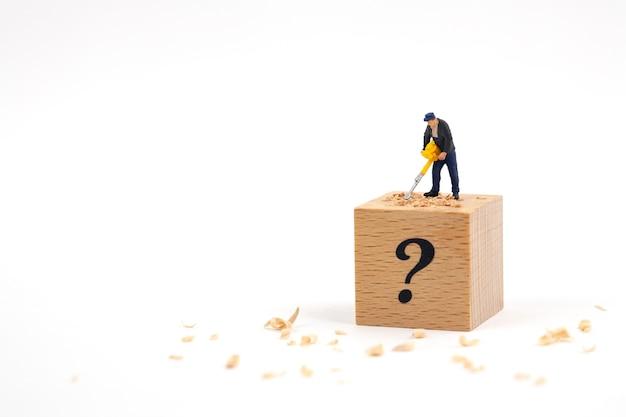 Hombre miniatura cavando un cubo de madera con un taladro