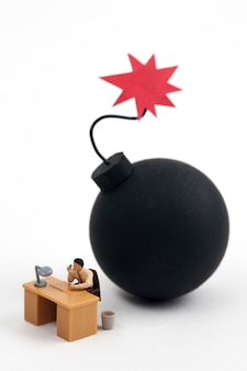 Hombre miniatura trabajando con bomba lista para explotar