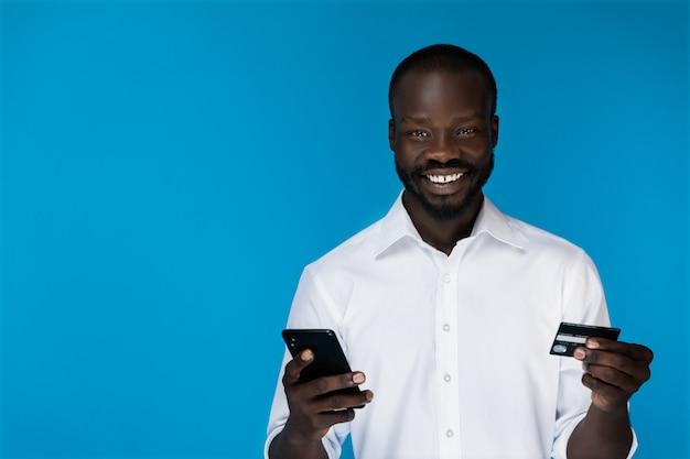 El hombre mira a la cámara y sostiene un teléfono y una tarjeta de crédito