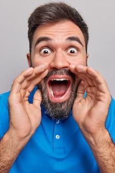 El hombre mira fijamente los ojos saltones mantiene la boca ampliamente abierta susurra en secreto muy sorprendido por las noticias vestido con camiseta azul aislado en gris