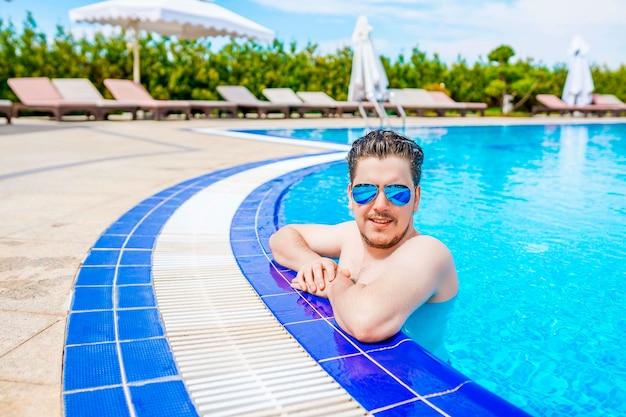 Un hombre mira fuera de la piscina, colgado en la barandilla.