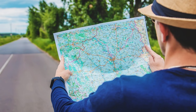 Un hombre mira un mapa en la carretera.