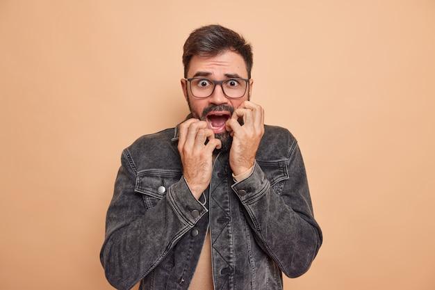 El hombre mira con pánico, tiembla de miedo, miedo a algo, tiene las manos en la cara, mantiene la mandíbula caída, lleva gafas y una chaqueta de mezclilla en un estudio beige