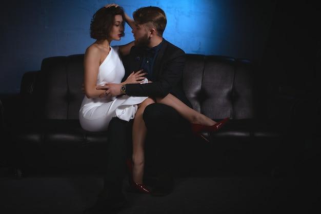 El hombre mira con pasión a la joven que puso los pies sobre sus rodillas.