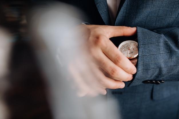 El hombre mira el reloj en su mano