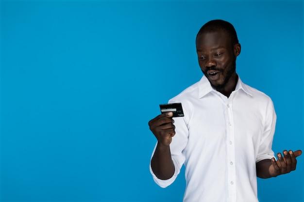 El hombre mira la tarjeta de crédito y muestra sus emociones.