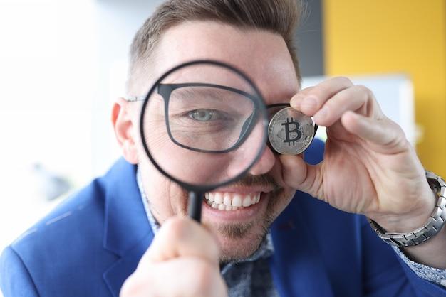El hombre mira a través de una lupa y tiene bitcoin en su mano ganancias en criptomonedas