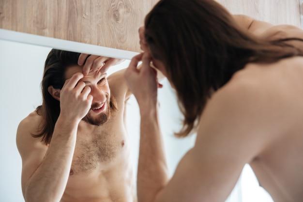 Hombre mirando al espejo y apretando espinillas en el baño.