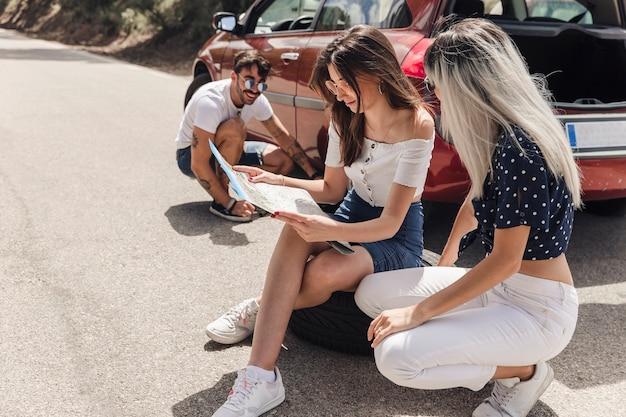 Hombre mirando a amigas mirando el mapa cerca del coche averiado en el camino