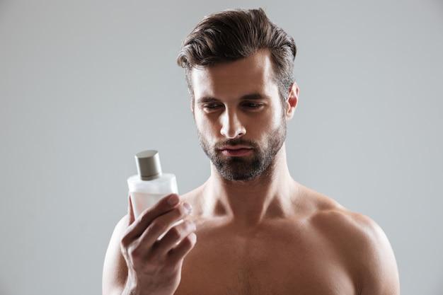 Hombre mirando la botella de perfume aislado