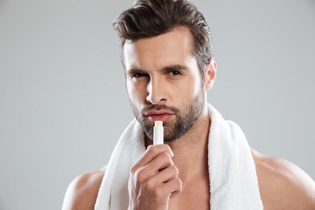 Hombre mirando la cámara y usando lápiz labial